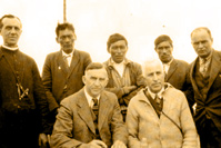 The signing of the Treaty at Winisk, Ontario. Left to right, standing: Father Martel, Indians John Bird, Xavier Patrick and David Sutherland, Dr. O'Gorman and J. Harris, H.B. Co. Post Manager. Seated: Commissioners Walter C. Cain and H. N. Awrey. July 28, 1930.